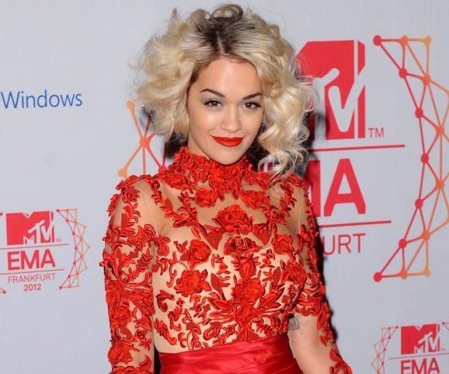 Foto Rita Ora con pelo corto rizado como peinado para cabellos rizados