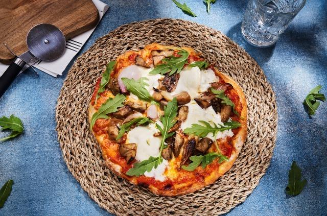 Foto Pizza con mozzarella, boletus y cebollas asadas
