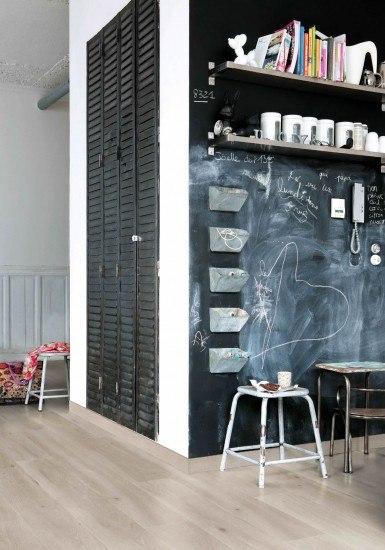 Foto Cocina blanca con una pared de pizarra negra, ideal para un piso de estudiantes