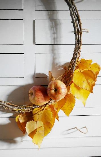 Foto Corona rústica otoñal con ramas, hojas y manzanas